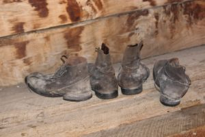 four old brown dusty shoes on a wooden bench