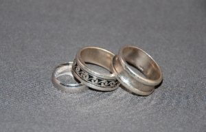 Three wedding rings stacked on a dark background